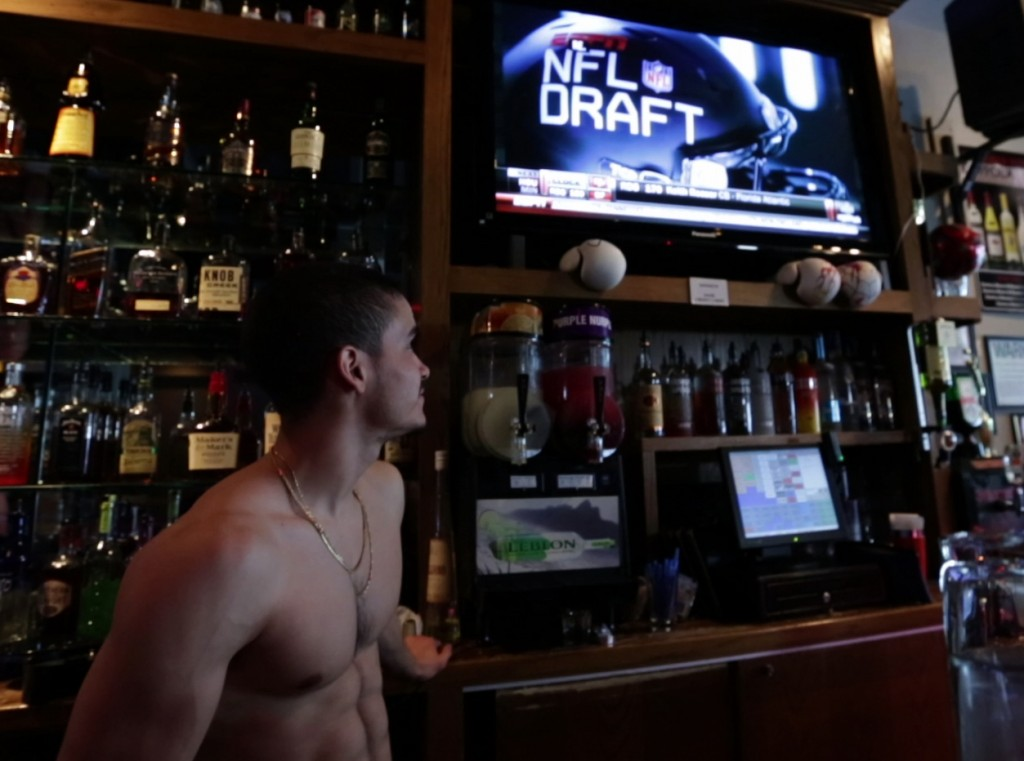 A bartender at NYC gay sports bar Boxers nervously watches the 2014 NFL Draft.